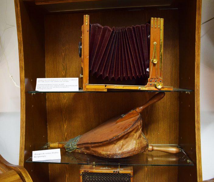 sus (Aparat de fotografiat cu burduf de Carl Zeiss, 1898 cu obiectiv de 180 mm) jos (Pompă de mână cu foale) Cea de-a doua sală conține expoziții definitorii pentru întemeierea Universității Babeș-Bolyai.