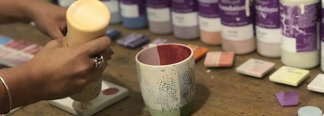 Pe o masă dintr-o încăpere alăturată sunt pregătite diverse culori pentru pictură, unde oamenii merg să își aleagă culorile dorite.
