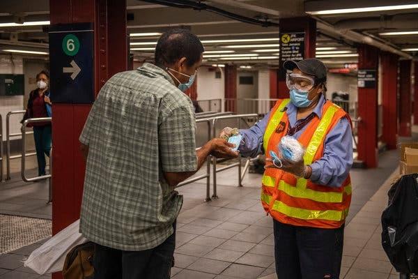 Yvette Johnson, un angajat al metroului împarte măști pentru călători. Sursă foto: Brittainy Newman for The New York Times